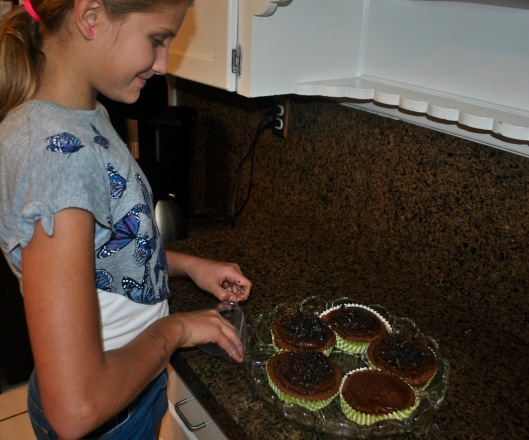 sprinkling crushed cookie crumbs onto the cupcakes