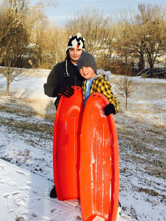the boys sledding at the park